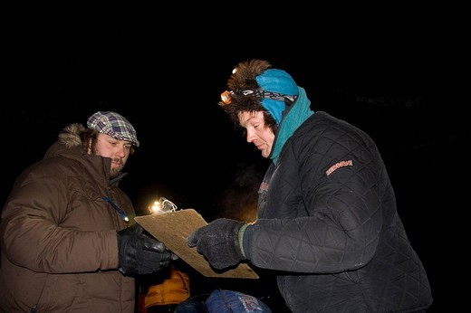 Yukon Quest Sled Dog Race musher and challenger Ken Anderson, signing an official paper before leaving Dawson City, Yukon Territory, Canada : Stock Photo