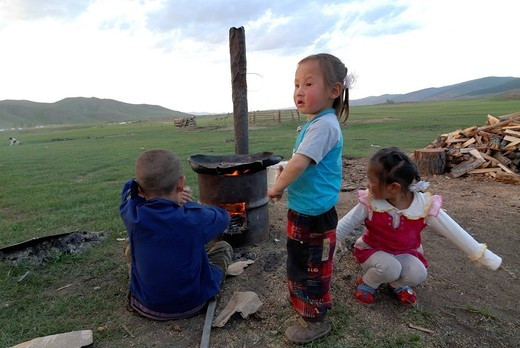 Children playing in the grasslands in front of a simple oven at the Orkhon Waterfall, Orkhon Khuerkhree, Kharkhorin, Oevoerkhangai Aimak, Mongolia, Asia : Stock Photo
