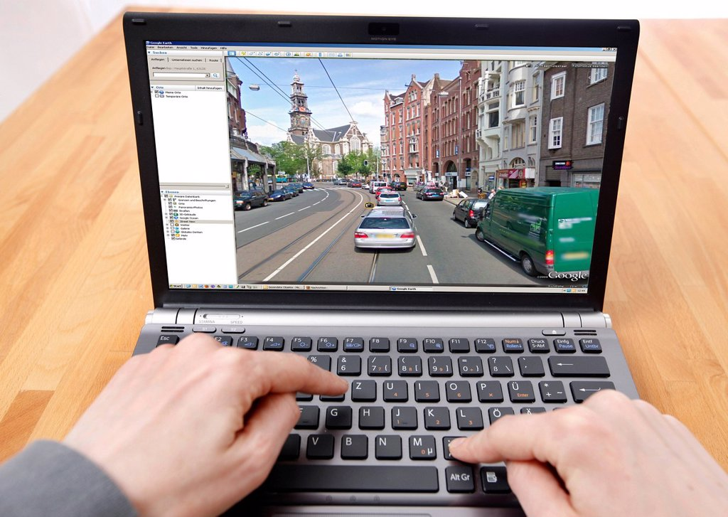 Person sitting at a computer working with Google Street View, screen showing a detailed image of part of the city centre of Amsterdam, people and licence plates have been obliterated : Stock Photo
