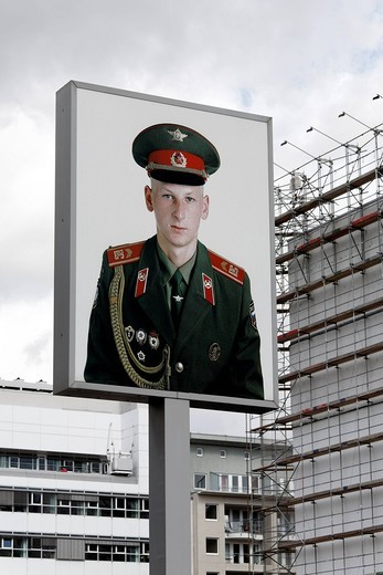 Advertising billboard with a large photo of a soldier wearing the uniform of the former Soviet army, Checkpoint Charlie, Berlin_Mitte, Germany, Europe : Stock Photo