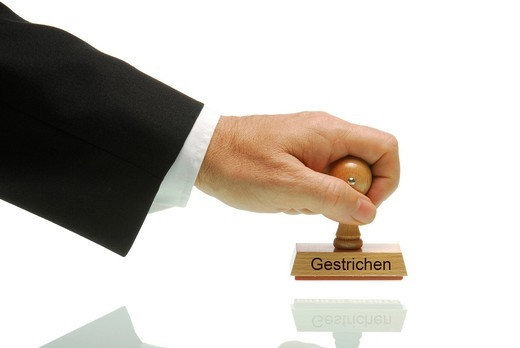 Stock Photo: 1848-544254 Arm of a businessman holding a stamp with the message Gestrichen, German for cancelled