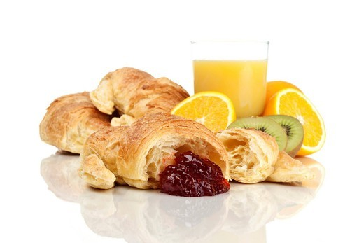 Croissants with strawberry jam, juice and fruit : Stock Photo