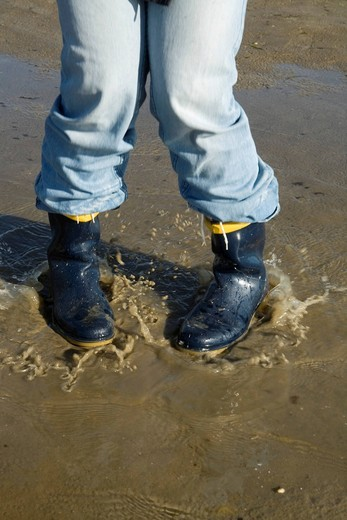 Jumping in a puddle with rubber boots : Stock Photo