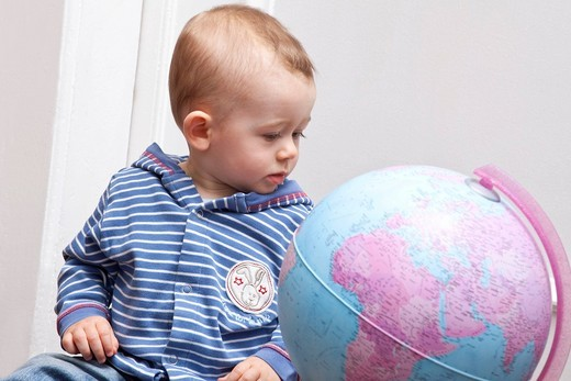 Boy, baby, eight months, with globe : Stock Photo