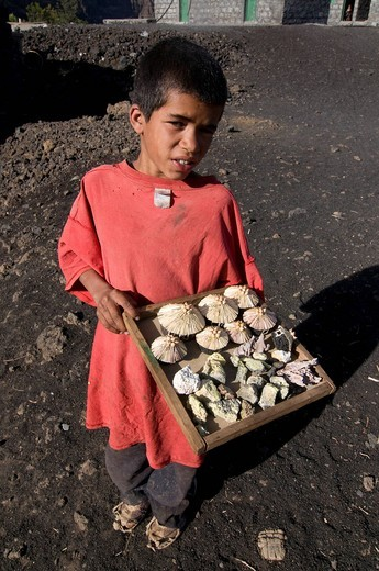 Native boy selling something in front of his house near a volcano, Fogo, Cabo Verde, Africa, : Stock Photo