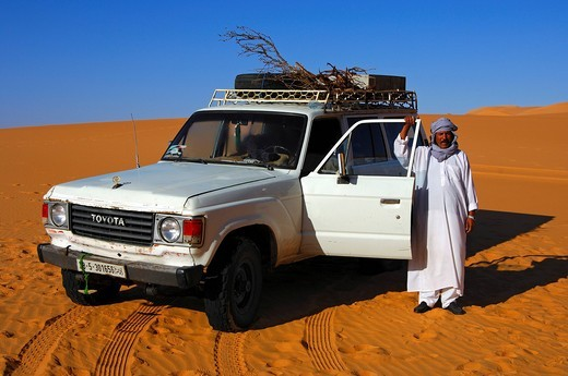 Bedouin posing in front of his Toyota jeep in the desert, Ubari Sand Sea, Sahara, Libya, North Africa : Stock Photo