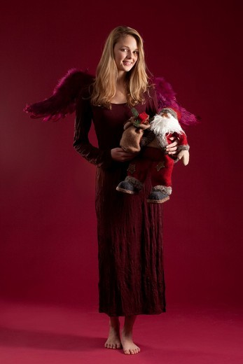 Stock Photo: 1848-547381 Blonde red_dressed angel with Santa Claus doll