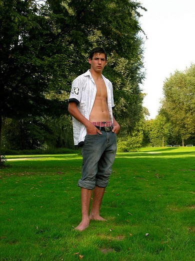 16_year_old boy wearing an unbuttoned shirt in a park : Stock Photo