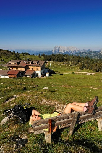 Hiker resting on the Eggenalm mountain pasture near the Straubinger Haus alpine lodge, in the back Mt. Wilder Kaiser, Reit im Winkl, Chiemgau, Upper Bavaria, Bavaria, Germany, Tyrol, Austria, Europe : Stock Photo