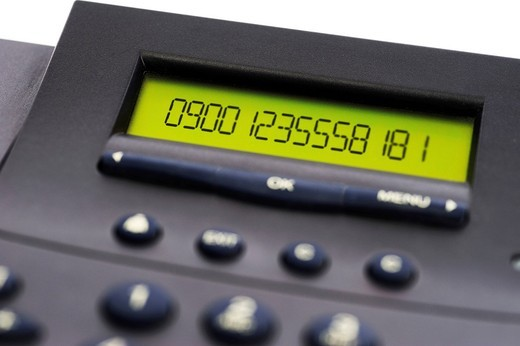 Telephone displaying a phone number beginning with 0900 : Stock Photo