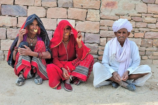 Two Indian women with golden nose_rings and an elderly Indian man wearing a turban sitting in traditional clothing on the floor in front of a stone wall, Bishnoi ethnic group, Thar Desert, Rajasthan, India, Asia : Stock Photo
