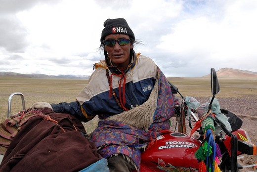 Tibetan pilgrim wearing sunglasses while sitting on a decorated and packed motorcycle on the way to Mount Kailash, in the high altitude plateau of Changtang near the Lungkar Mountains, Western Tibet, Ngari Province, Tibet, China, Asia : Stock Photo