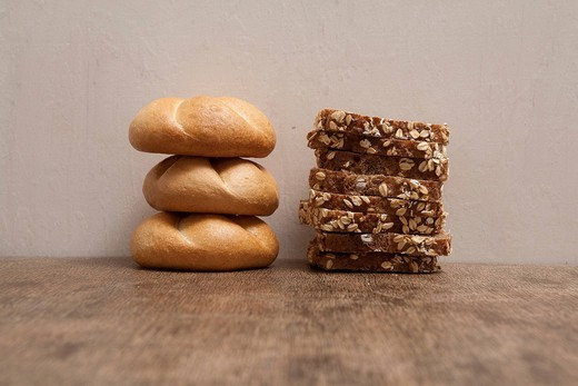 Stacks of bread rolls and sliced bread : Stock Photo