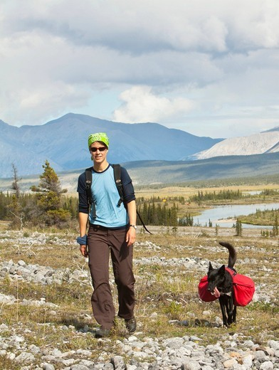 Young woman hiking, pack dog, Alaskan Husky, sled dog, carrying a dog pack, backpack, Wind River and Mackenzie Mountains behind, Yukon Territory, Canada : Stock Photo