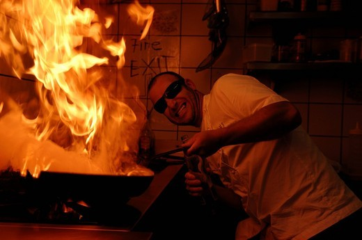 Man with sunglasses holding a burning pan on the stove : Stock Photo
