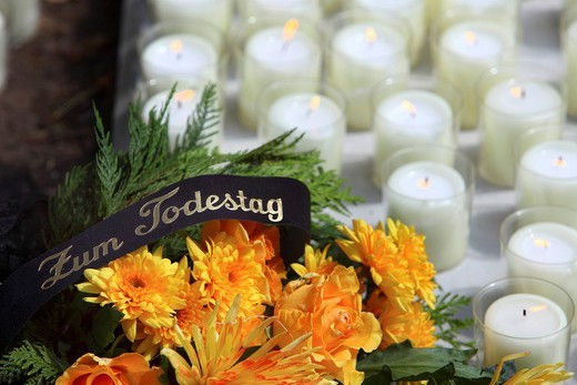 Lettering Zum Todestag, German for in commemoration of the anniversary of the death, a wreath of flowers on a grave, white candles : Stock Photo