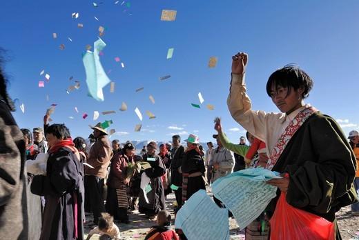 Stock Photo: 1848-553655 Tibetan pilgrims throwing prayer notes into the air, ceremony at Namtso Lake, Heavenly Lake, Tibetan, China, Asia