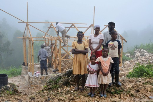 A family, victims of the earthquake in january 2010, next to their new earthquake_proof house with truss structure, which is made available by a German aid organization, Coq Chante village near Jacmel, Haiti, Caribbean, Central America : Stock Photo