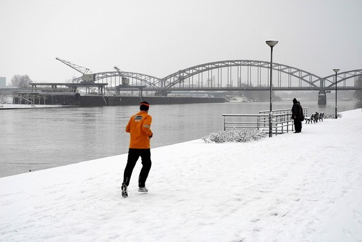 Jogger running on the snowy bank of the Main River, Deutschherrn Ufer quay, the Deutschherrn railway bridge at the back, Frankfurt am Main, Hesse, Germany, Europe : Stock Photo