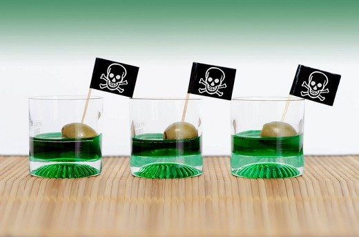 Three glasses with alcohol and skull flags, symbolic image for binge drinking : Stock Photo
