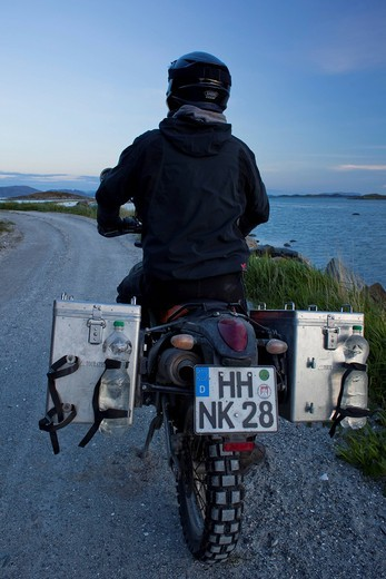 Stock Photo: 1848-555632 Man riding an Enduro motorcycle along the Norwegian coast in the evening twilight, Gimsefjorde, Norway, Scandinavia, Europe