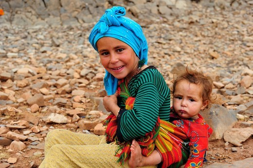 Girl wearing a headscarf carrying her little brother in a sling, High Atlas Mountains, Morocco, Africa : Stock Photo