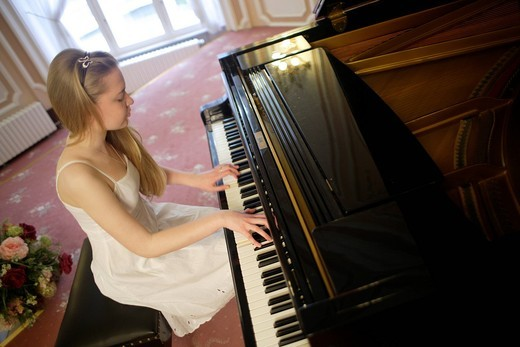Woman in a white dress playing a grand piano : Stock Photo