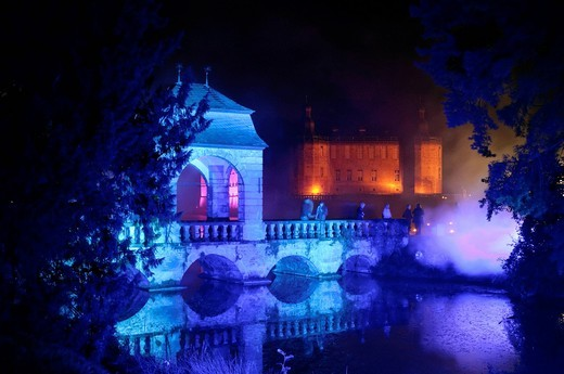 Blue floodlit bridge at the Illumina at Schloss Dyck, Juechen, Neuss, North Rhine_Westphalia, Germany, Europe : Stock Photo