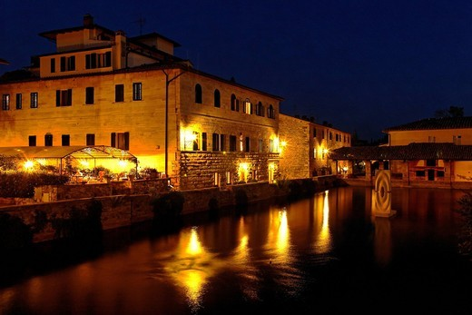 The basin of hot sulphur spring in Bagno Vignoni and Hotel Le Terme at night, Orcia Valley, Tuscany, Italy, Europe : Stock Photo