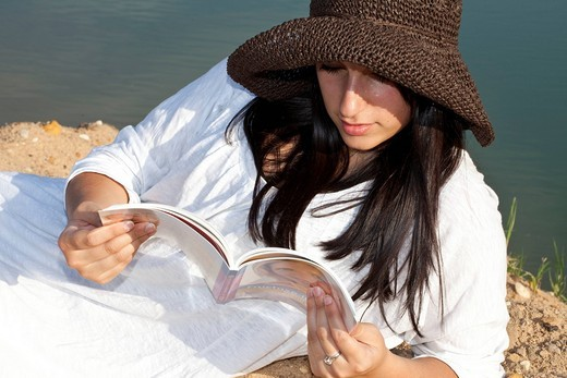 Stock Photo: 1848-557914 Young woman wearing a straw hat sitting on the beach of a quarry pond and reading a book