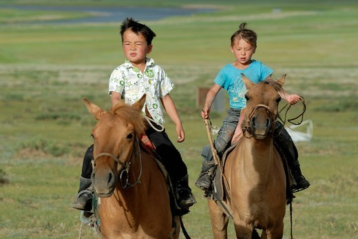 Two small 6_year_old Mongolian boys breaking in spirited Mongolian horses in the dry grasslands, Lun, Toev Aimak, Mongolia, Asia : Stock Photo
