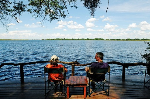 Tourists sitting on the terrace of a lodge on the Guma Lagoon, Okavango Delta, Botswana, Africa : Stock Photo