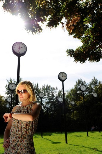 Young woman waiting for an appointment or rendezvous looking at her wristwatch : Stock Photo