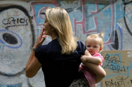 Young woman smoking a cigarette, little girl, 2 years : Stock Photo