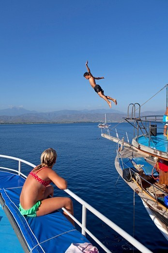 Teenager jumping from a boat, Red Island, Turkish Aegean, Turkey, Asia : Stock Photo