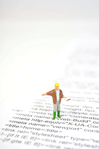 Stock Photo: 1848-560836 Figurine standing on the source code of a website