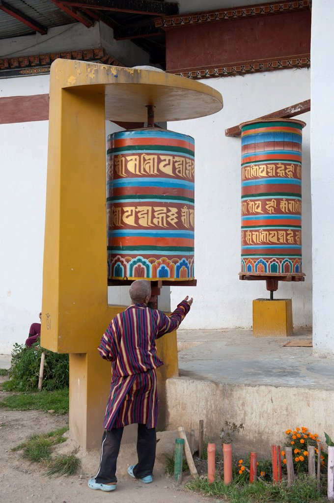 Stock Photo: 1848-561986 Tibetan Buddhism, believer spinning a large modern prayer wheel, Thimphu, the Himalayas, Kingdom of Bhutan, South Asia, Asia