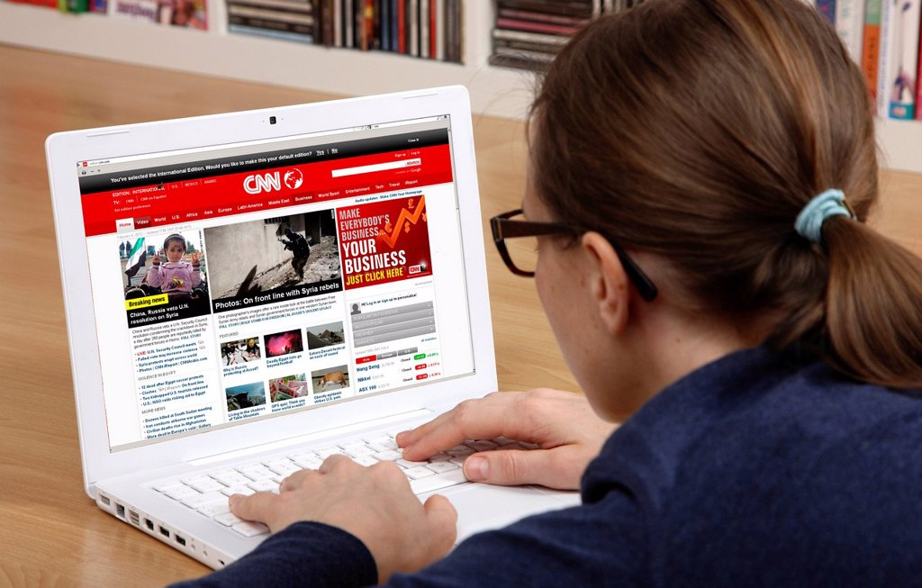 Woman surfing the internet with a laptop, website of the US news channel CNN : Stock Photo