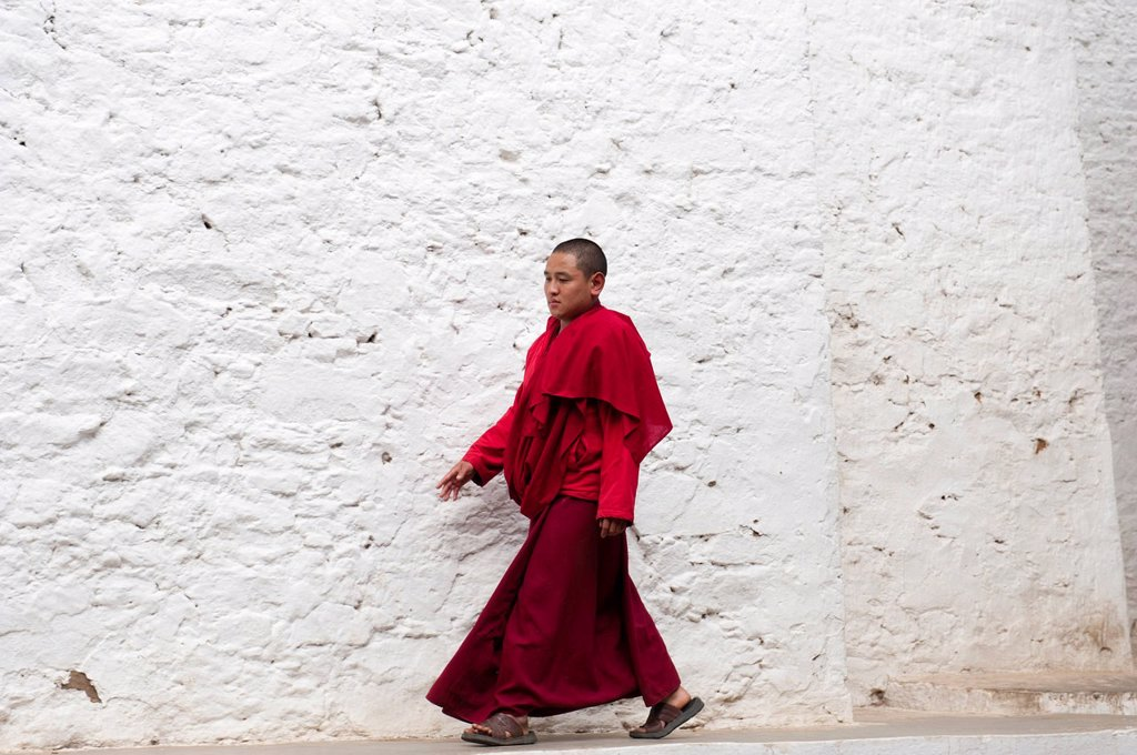 Stock Photo: 1848-562470 Tibetan Buddhism, monk in a red robe walking in front of a white wall, Tango Goemba Monastery, near Thimphu, the Himalayas, Kingdom of Bhutan, South Asia, Asia