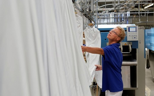 Stock Photo: 1848-5627 Rosalie Herr working with a folding and spreading machine in the white section of an industrial laundry, Bardusch Uniform Rental & Laundry Services, Textil_Mietdienst Bardusch GmbH in Ettlingen, Baden_Wuerttemberg, Germany, Europe