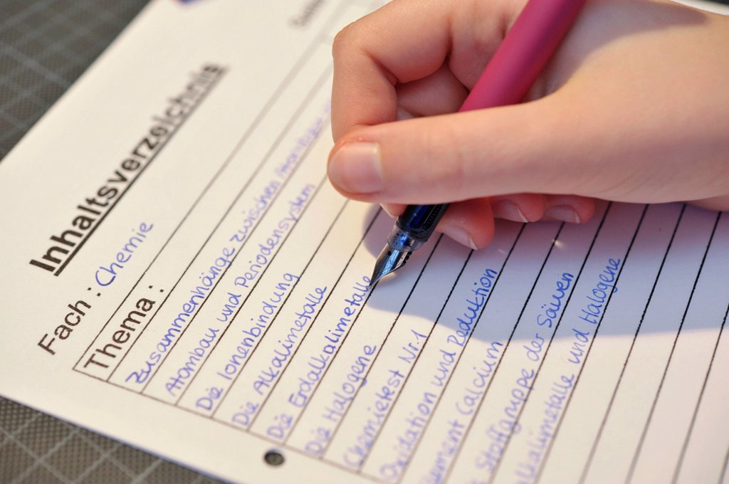 Stock Photo: 1848-562755 School pupil writing a table of contents for the subject of chemistry
