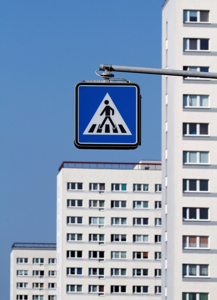 Pedestrian crossing sign in front of apartment buildings : Stock Photo