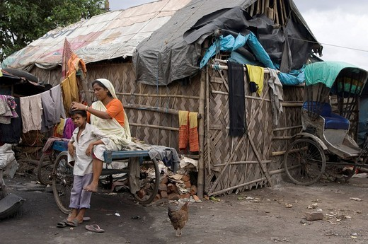 Mother looking through her son´s hair, searching for lice in the slums of Howrah, Hooghly, West Bengal, India : Stock Photo