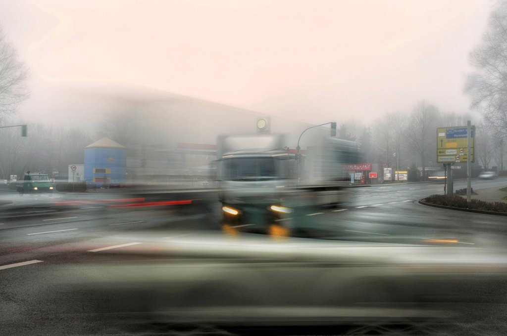 Trucks and cars at an intersection in the morning mist, motion blur : Stock Photo