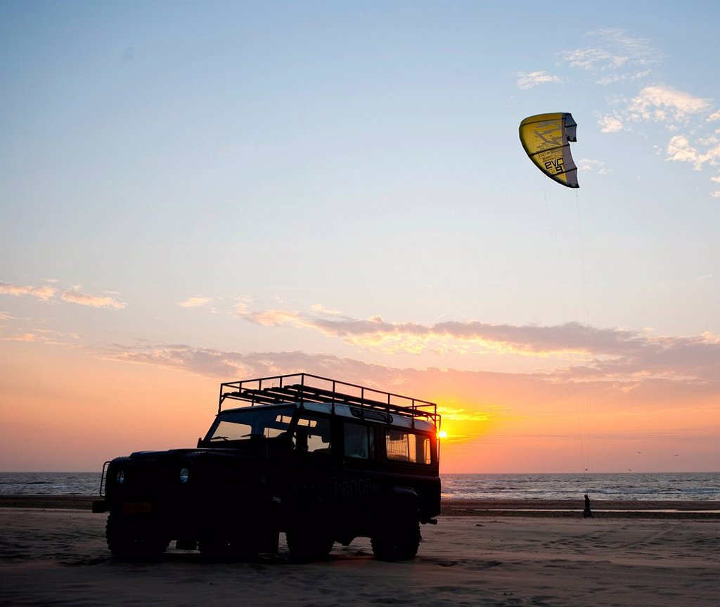 Stock Photo: 1848-568040 Silhouette of an off_road vehicle and a kite surfer on the beach of Egmond aan Zee at sunset, Netherlands, Europe