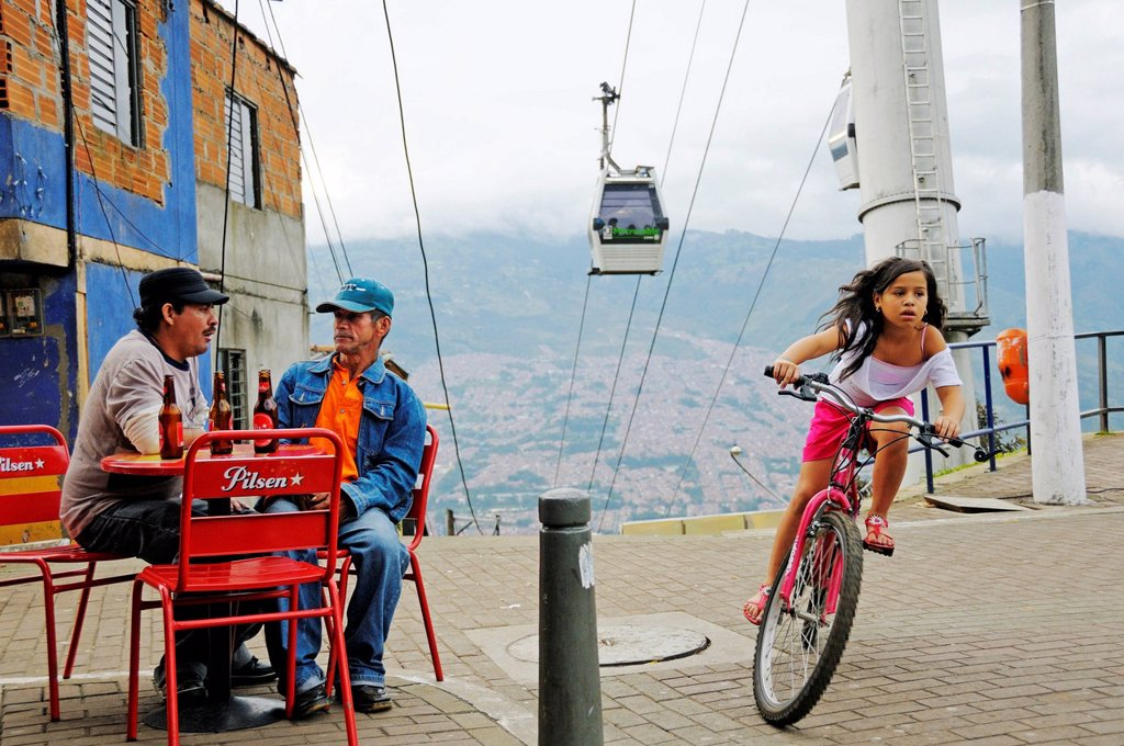 Men sitting in a street café, girl riding a bicycle, Metrocable cable car at back, slums, Comuna 13, Medellin, Colombia, South America, Latin America, America : Stock Photo