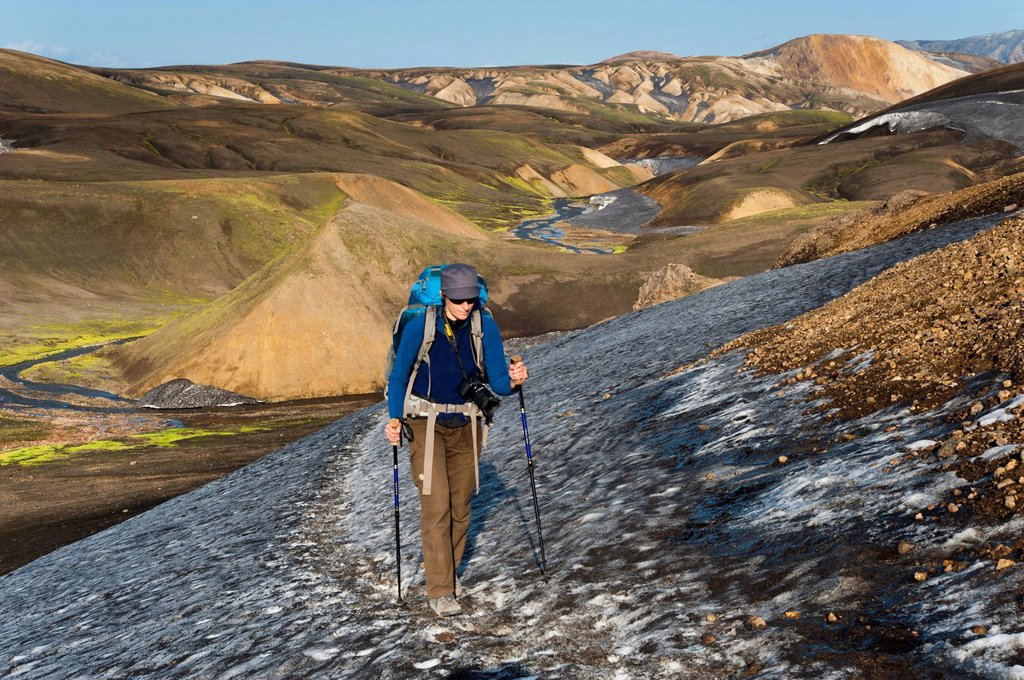 Female hiker walking on a snow field, rhyolite mountains covered with ash and snow on the Laugavegur hiking trail, Landmannalaugar Hrafntinnusker, Fjallabak Nature Reserve, Highlands of Iceland, Iceland, Europe : Stock Photo