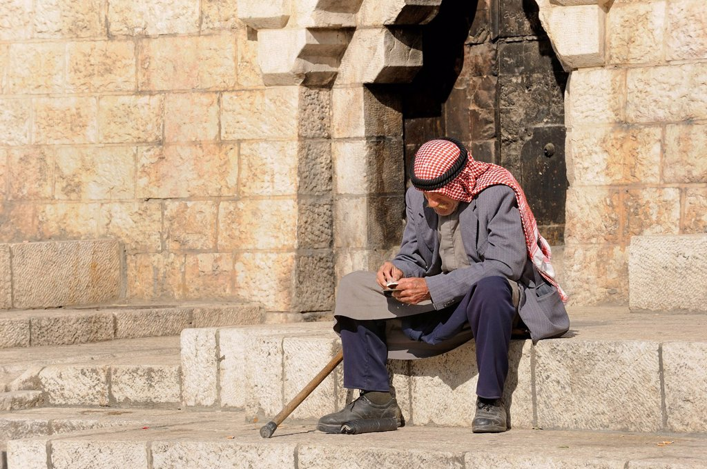 Stock Photo: 1848-568752 Palestinian man with keffiyeh or kafiya sitting on his own on the steps of the Damascus Gate, Old City, Jerusalem, Israel, Middle East