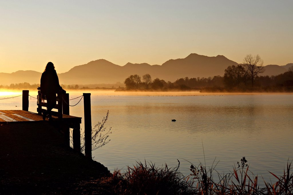 Stock Photo: 1848-568837 Silhouette of a woman sitting on a pier overlooking lake Chiemsee at sunrise, Chiemgau, Upper Bavaria, Germany, Europe