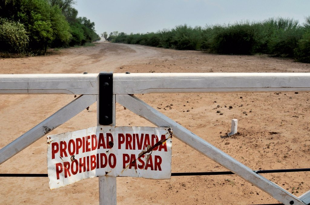 Stock Photo: 1848-570053 Sign on a gate ´´Propiedad privada, Prohibido pasar´´, ´´private property, access prohibited´´, marking the grounds of a major landowner in the Gran Chaco region, Salta province, Argentina, South America